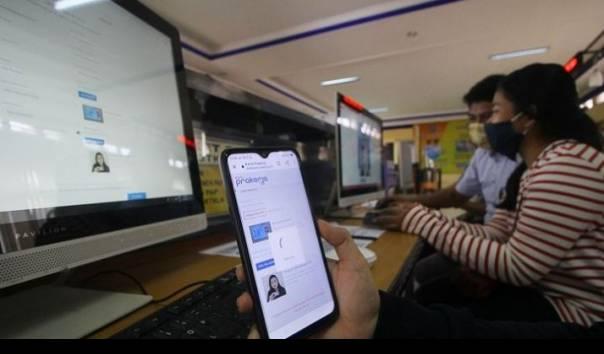 Petugas mendampingi warga yang melakukan pendaftaran calon peserta Kartu Prakerja di LTSA-UPT P2TK di Surabaya, Jawa Timur, Senin (13/4/2020
